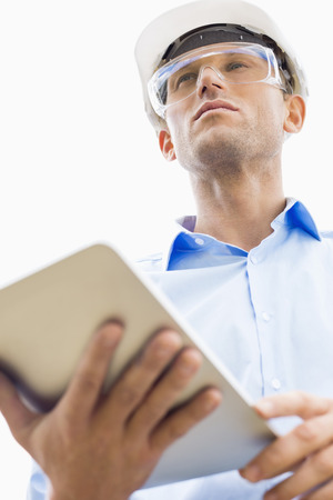 Low angle view of male architect holding tablet PC against sky Stock Photo - 25344676