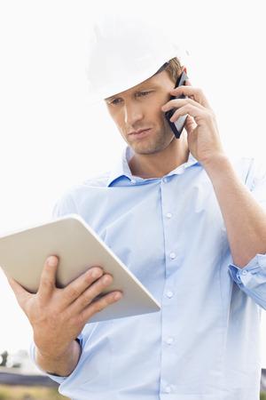 デジタル タブレットのサイトで携帯電話を使用しての男性建築家 写真素材