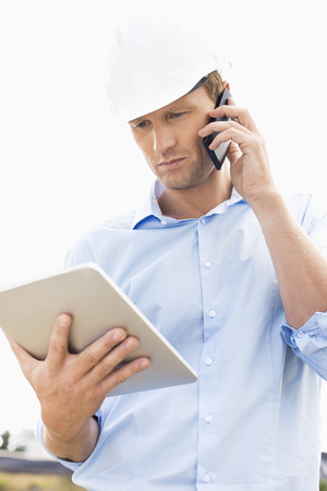 Male architect with digital tablet using cell phone at site Standard-Bild