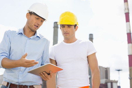 construction safety: Male construction workers discussing over digital tablet at industry LANG_EVOIMAGES