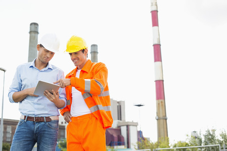 Two construction workers discussing over tablet PC at industry Stock Photo - 25345606