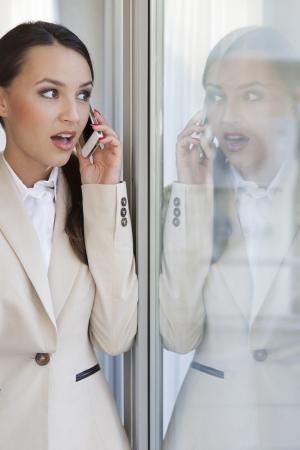 Femme d'affaires choqué à l'aide de téléphone portable au bureau