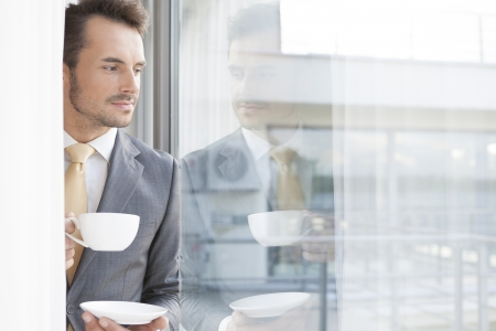 window view: Thoughtful businessman having coffee in office