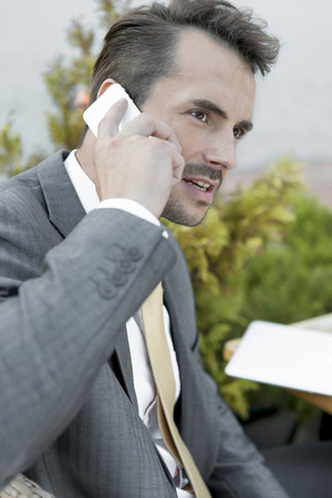 Businessman answering cell phone outdoors Stock Photo