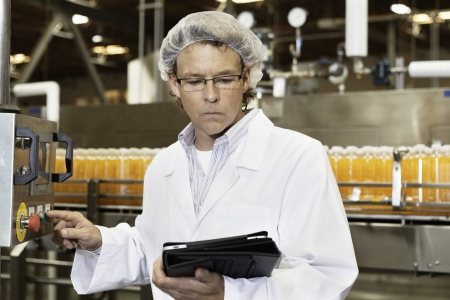 瓶詰め工場で作業しながらタブレット PC を見ている男