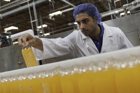 Mid adult industrial worker looking at bottle in factory 写真素材