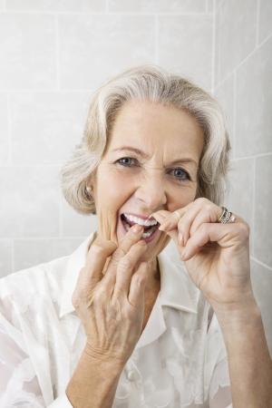 flossing: Portrait of senior woman flossing teeth in bathroom