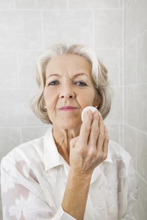 powder room: Portrait of senior woman applying face powder in bathroom