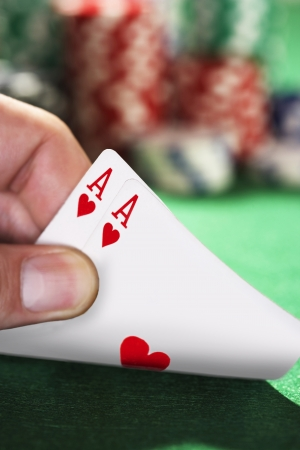 Closeup of hand peeked at two playing cards