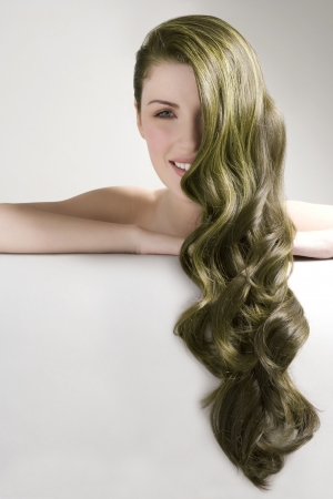 the green: Beautiful woman with long green dyed hair against gray background LANG_EVOIMAGES