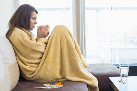 Side view of sick woman having coffee on sofa in living room