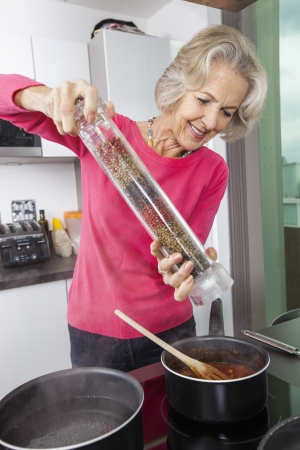 pepper grinder: Senior woman cooking food using pepper grinder