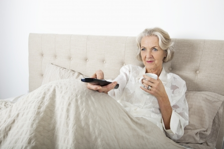 woman watching tv: Senior woman watching TV while having coffee in bed