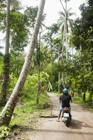 unpaved road: Rear view of young man riding scooter on an unpaved road; Koh Pha Ngan; Thailand LANG_EVOIMAGES
