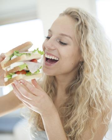 femme bouche ouverte: Femme heureuse de manger gros sandwich dans la maison LANG_EVOIMAGES