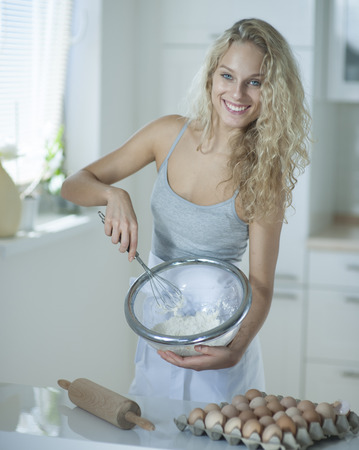 czech women: Portrait of woman mixing cookie batter in kitchen at counter LANG_EVOIMAGES