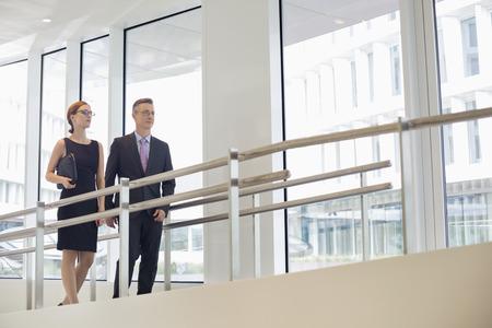 walking away: Business people walking by railing in office