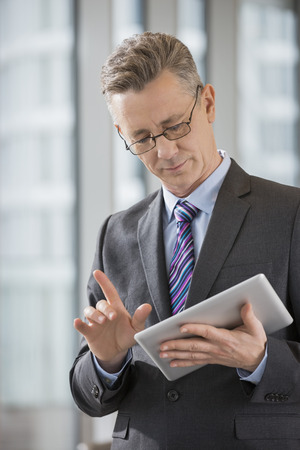 business: Businessman gesturing while using digital tablet in office