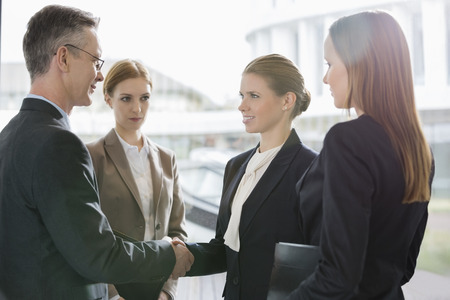 Confident business people shaking hands at workplace Stock Photo