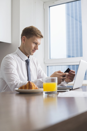 eating breakfast: Mid adult businessman using cell phone with laptop on breakfast table LANG_EVOIMAGES