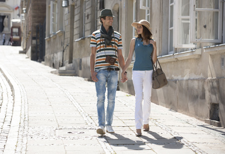 holding hands while walking: Tourist couple holding hands while walking on sidewalk