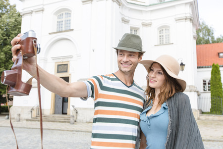 casimir: Tourist couple taking self portrait outside St. Casimir Church; Warsaw; Poland