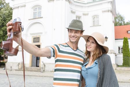 casimir: Tourist couple taking self portrait outside St. Casimir Church; Warsaw; Poland