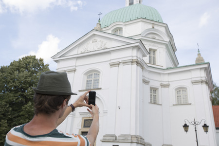 casimir: Rear view of young man photographing St. Casimir Church; Warsaw; Poland