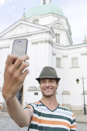 casimir: Young man taking self portrait outside St. Casimir Church; Warsaw; Poland
