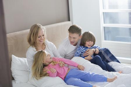 girl bedroom: Parents playing with children in bedroom