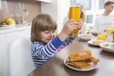 家族で朝食をとりながらワッフルに蜂蜜を注ぐ幸せな少年