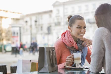 sidewalk talk: Female friends at sidewalk cafe