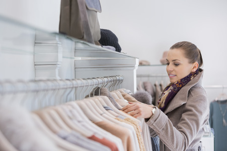 clothing rack: Side view of young woman choosing sweater in store