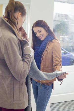 decisionmaking: Female friends choosing sweater in store