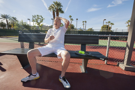 player bench: Tired senior tennis player relaxing on bench at court