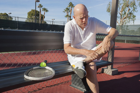 player bench: Senior male tennis player with leg pain sitting on bench at court