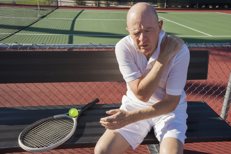 pain: Senior male tennis player with shoulder pain sitting on bench at court