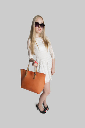 mini purse: Portrait of fashionable girl carrying purse over gray background