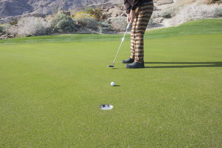 golf of california: Low section of senior male golfer putting ball into hole at golf course