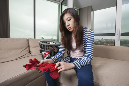 laundry room: Young woman doing laundry work in living room at home