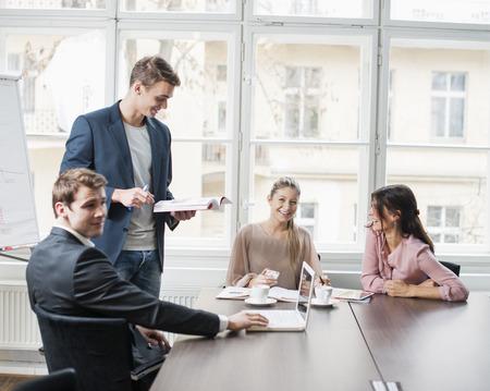 empleado de oficina: Los j�venes empresarios que miran la computadora port�til en la reuni�n