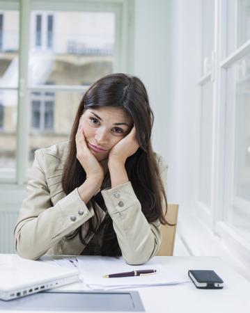 czech women: Portrait of bored businesswoman sitting at desk in office