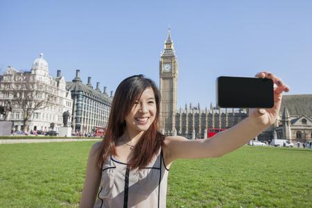 self   portrait: Young woman taking self portrait through smart phone against Big Ben at London; England; UK