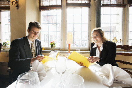 decisionmaking: Portrait of smiling business couple with menus at restaurant table
