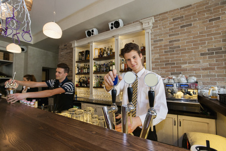 beer tap: Portrait of confident bartender at counter with coworkers in background