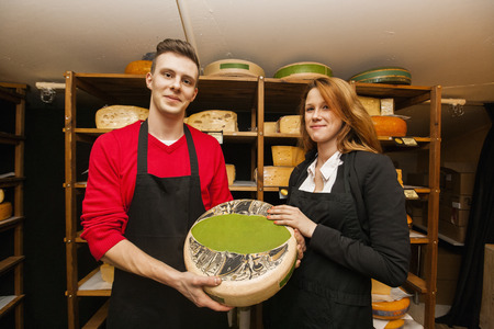 salespeople: Portrait of confident salespeople showing cheese in shop LANG_EVOIMAGES