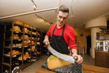 the clerk: Cortar el queso en el mostrador joven empleado de la tienda LANG_EVOIMAGES
