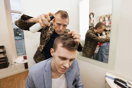 hairspray: Professional barber using hairspray on male customer in shop LANG_EVOIMAGES