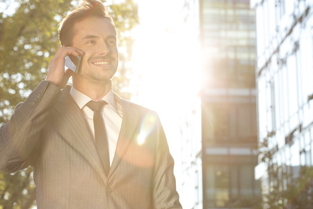 attire: Happy young businessman using cell phone outdoors