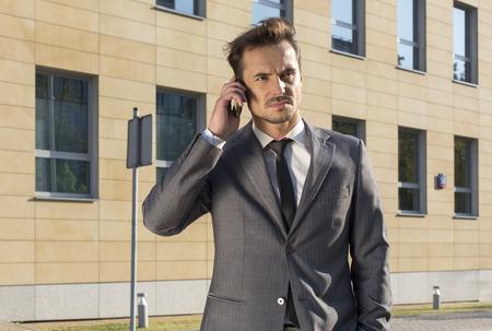 sidewalk talk: Businessman using cell phone against office building